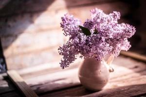 Blumenstrauß von Flieder auf hölzernem Hintergrund