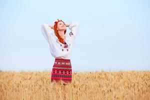 rothaariges Mädchen in der ukrainischen nationalen Kleidung auf dem Weizenfeld.