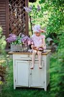 niedliches Kindermädchen, das Fliederkranz im blühenden Garten des Frühlings macht