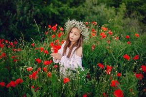 schönes kleines Mädchen, das in einem Rockkranz von Mohnblumen aufwirft