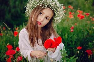 schönes kleines Mädchen, das im Rock einen Kranz von Mohnblumen aufwirft