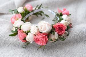 Tiara der künstlichen Rosen auf hölzernem Hintergrund.