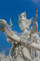 thailändische weiße Skulptur mit Lotusblumen in den Händen