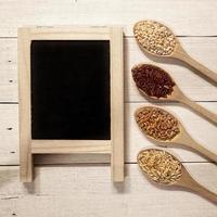 Müsli in den Löffeln und Tafel auf Holztisch