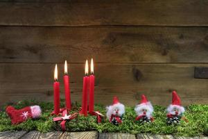 vier rote brennende Weihnachtskerzen auf hölzernem Hintergrund.