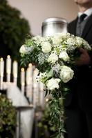 ein Mann mit Urne und Blumen bei einer Beerdigung