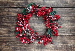 Holly Weihnachtskranz auf Holztisch. foto
