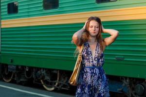 Frau wartet Zug auf dem Bahnsteig
