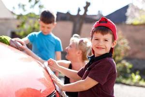 glückliches kleines Kind Autowäsche mit Familie