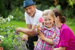 Mädchen im Garten mit Oma und Vater, die Blume zeigen foto