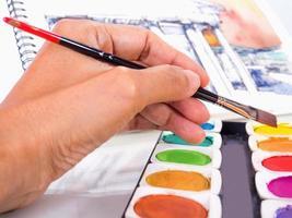 Hand des Designers, der mit Künstlerausrüstung arbeitet foto