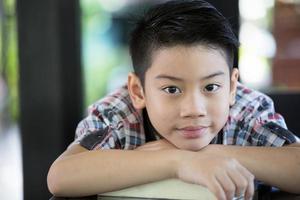 asiatischer Junge ist kleines Lächeln und schauende Kamera
