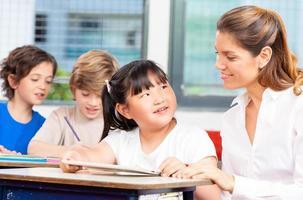 glückliche multiethnische Grundschüler mit Lehrer