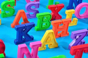 bunte Alphabetbuchstaben aus Kunststoff auf blauem Grund
