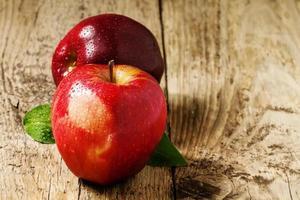 zwei rote Äpfel mit Wassertropfen auf einem Holztisch
