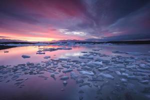 Eisberge, die im Fjallsarlon-Gletschersee bei Sonnenuntergang schwimmen