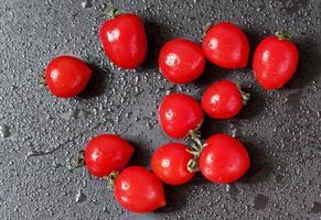 Tomaten mit Wassertropfen auf dunklem Hintergrund, selektiver Fokus foto