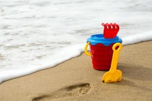 roter Eimer mit Schaufel, Rechen und Netz am Strand