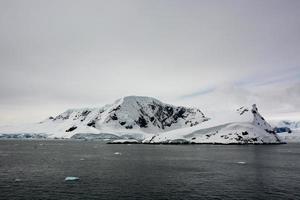schneebedeckter schwarzer Berg in der Antarktis foto
