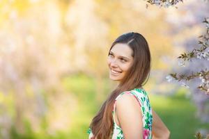 schöne brünette Frau im blühenden Obstgarten