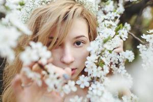 Porträt eines schönen Mädchens, das Bäume blüht foto