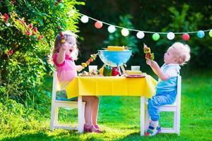 Gartengrillparty für zwei glückliche Kinder foto