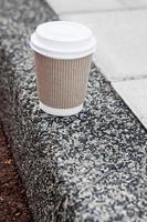 Einwegkaffeetasse auf Bürgersteig mit Stadt im Hintergrund