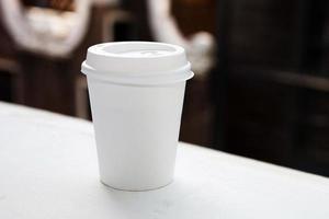 Einwegkaffeetasse auf Fensterbank mit Blick auf die Stadt im Hintergrund
