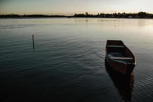 schäbiges Boot schwimmt abends auf ruhigem See