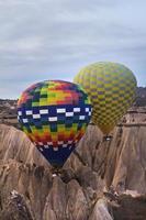 Heißluftballon, der über Felsenlandschaft am Kappadokien-Truthahn fliegt