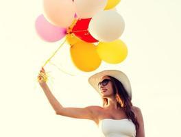lächelnde junge Frau in Sonnenbrille mit Luftballons foto