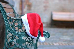 Weihnachtsmütze auf einer Bank foto