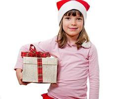 Kind mit Weihnachtsmannhut, der Geschenk hält foto