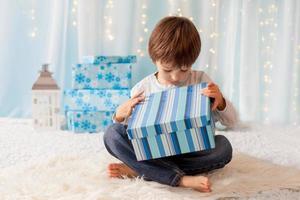 lächelndes lustiges Kind im roten Hut des Weihnachtsmanns, der Weihnachtsgeschenk hält foto
