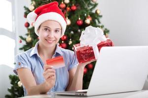 schöne Frau, die online für Weihnachten einkauft foto