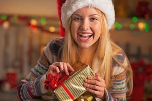 Porträt des Mädchens in der Weihnachtsmütze, die Weihnachtsgeschenkbox öffnet