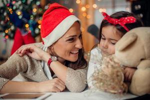 glückliche Mutter mit ihrer Tochter in Weihnachtsmannhüten foto
