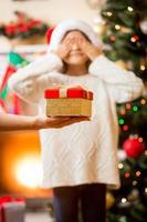 Mutter hält an Hand Weihnachtsgeschenk und gibt Tochter foto