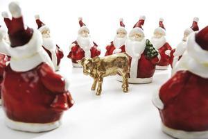 goldenes Kalb, umgeben von Weihnachtsmännern foto