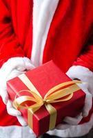 Weihnachtsmann zeigt eine Weihnachtsgeschenkbox foto
