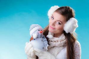 Frau in der warmen Kleidung, die Schneemannspielzeug hält.