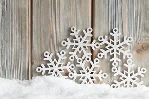 Schneeflocken auf Schnee und hölzernem Hintergrund