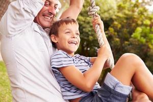 Vater schwingt mit Sohn auf einem Spielplatz foto