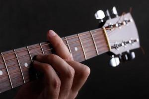 männliche Hand, die eine Barre auf der Gitarre hält foto