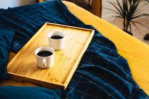 zwei Tassen Kaffee auf einem Tablett im Bett