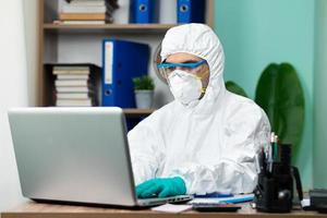 Mann mit weißer Schutzsuite, die am Laptop arbeitet foto