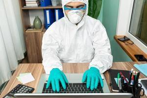 Mann mit persönlichem Schutzanzug, der am Computer arbeitet foto