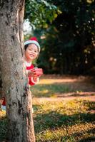 asiatisches Mädchen im roten Weihnachtsmannkostüm mit Geschenkbox