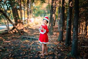 asiatisches Mädchen im roten Weihnachtsmannkostüm mit Geschenkbox foto