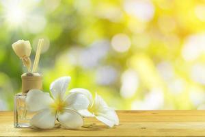 Parfümflasche mit weißen Blüten foto